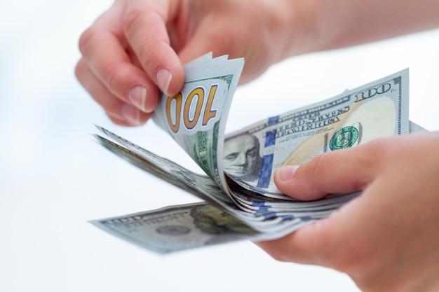 Persona cuenta billetes de dólares estadounidenses de cerca