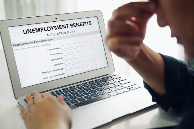 Persona deprimida desempleada que completa un formulario de solicitud de beneficios de desempleo en línea usando una computadora portátil.