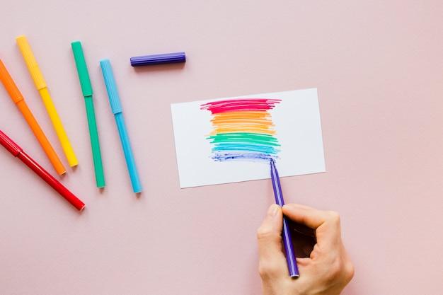 Persona dibujando arcoiris con rotulador