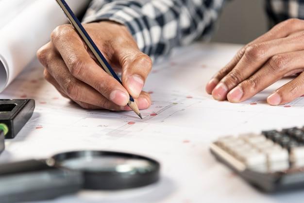 Persona dibujando un plano de una casa