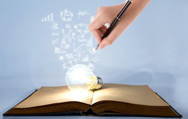 Persona dibujando símbolos que salen de una bombilla encendida encima de un libro