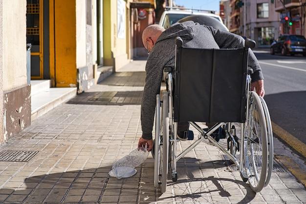 Persona discapacitada en silla de ruedas que recoge una botella de plástico transparente arrojada y abandonada en el piso para tirarla al contenedor de reciclaje de basura y evitar que se contamine. evita los plásticos