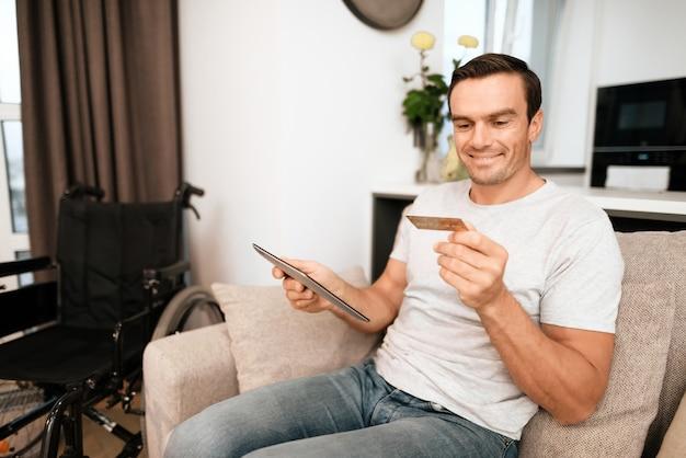 Persona discapacitada tiene tarjeta de crédito y usa tableta