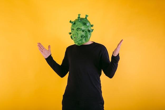 Persona disfrazada de coronavirus con máscara de látex virus covid abriendo los brazos sobre fondo amarillo concepto de coronavirus