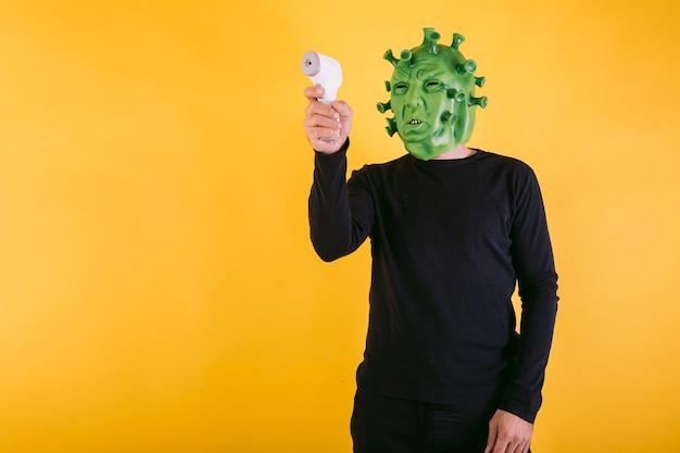 Persona disfrazada de coronavirus con máscara de látex virus covid apuntando un termómetro electrónico sobre fondo amarillo concepto de coronavirus