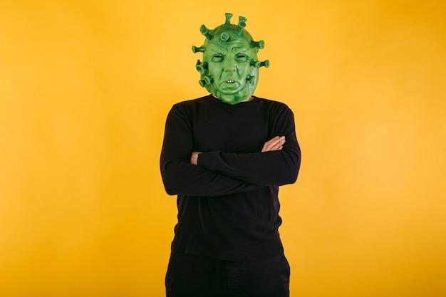 Persona disfrazada de coronavirus con máscara de látex virus covid con brazos cruzados sobre fondo amarillo concepto de coronavirus
