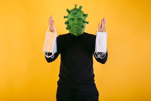 Persona disfrazada de coronavirus con máscara de látex virus covid con máscaras quirúrgicas sobre fondo amarillo concepto de coronavirus