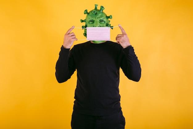 Persona disfrazada de coronavirus con máscara de látex virus covid poniéndose una máscara quirúrgica sobre un fondo amarillo concepto de coronavirus