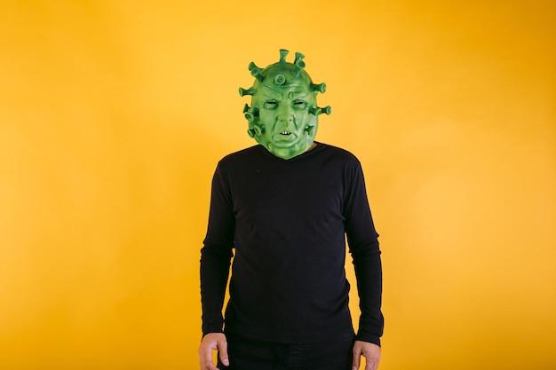 Persona disfrazada de coronavirus con máscara de látex virus covid sobre fondo amarillo concepto de coronavirus