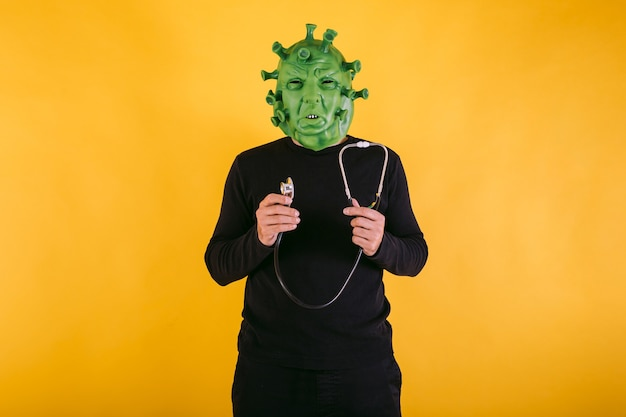 Persona disfrazada de coronavirus con máscara de látex virus covid sosteniendo un estetoscopio sobre fondo amarillo concepto de coronavirus