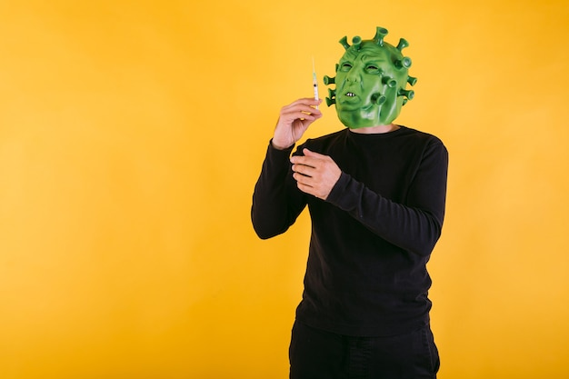 Persona disfrazada de coronavirus con máscara de látex virus covid sosteniendo una jeringa sobre fondo amarillo concepto de coronavirus