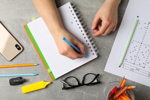 Persona escribe en un cuaderno sobre la superficie gris, vista desde arriba. concepto de examen