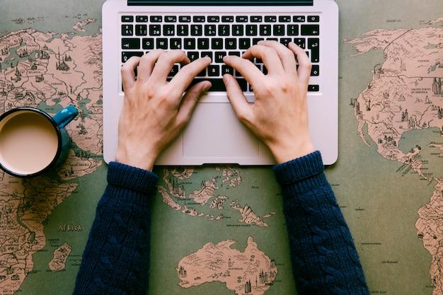 Persona escribiendo en la computadora portátil en el escritorio