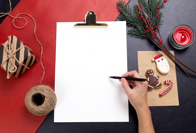 Persona escribiendo una nota con sabrosas galletas caseras de navidad