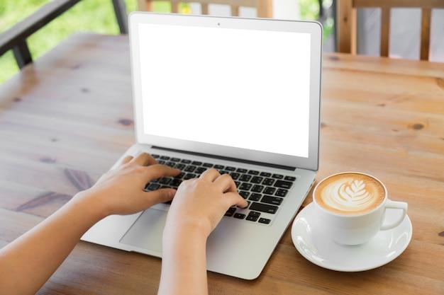 Persona escribiendo en un portátil con un café