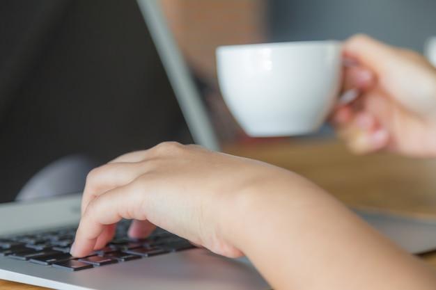 Persona escribiendo y sujetando una taza blanca