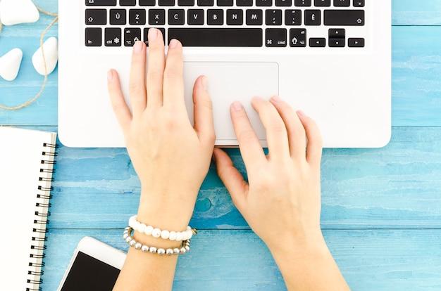 Persona escribiendo en el teclado del ordenador portátil