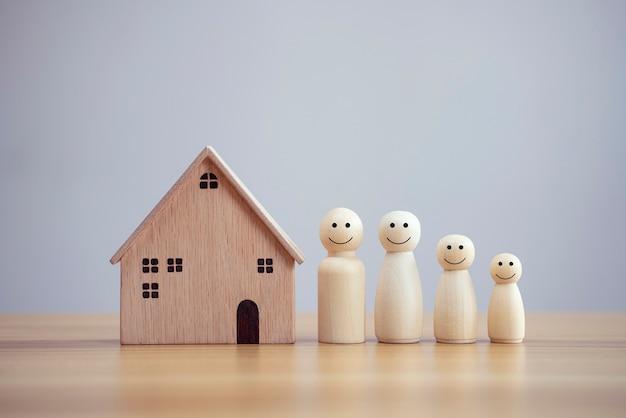 Persona de familia de madera feliz modelo un smiley y madera de la casa en el fondo de la tabla