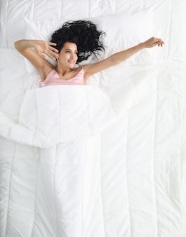 Persona feliz y alegre en la cama