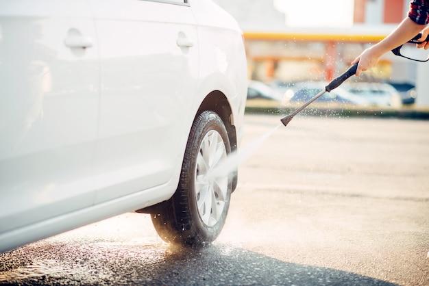 Persona femenina limpia las ruedas del coche con pistola de agua a alta presión. mujer joven en lavado de automóviles de autoservicio. lavado de vehículos al aire libre en verano.