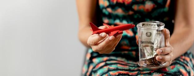 Persona con figurilla de avión y tarro transparente con dinero