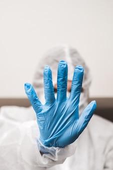 Persona con guantes de goma, máscara médica extiende su mano hacia adelante