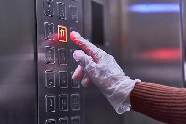 La persona con guantes de goma transparentes presiona el botón del elevador durante el brote de virus covid de la gripe, la epidemia de coronavirus y las enfermedades infecciosas
