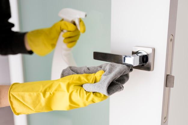 Persona con guantes de protección y haciendo tareas domésticas