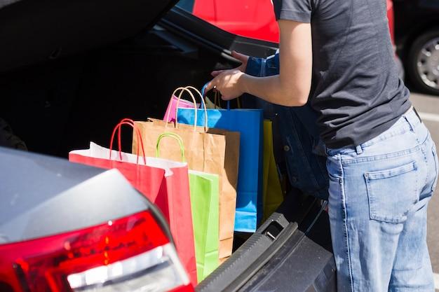 Persona guardando bolsas en el coche
