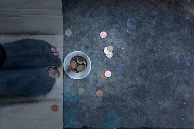 Persona sin hogar acostada plana con agujeros en sus calcetines