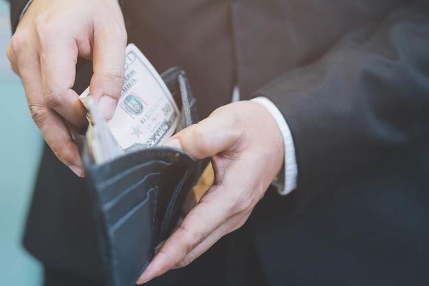 La persona del hombre de negocios que sostiene una cartera en las manos de un hombre saca el dinero del bolsillo.