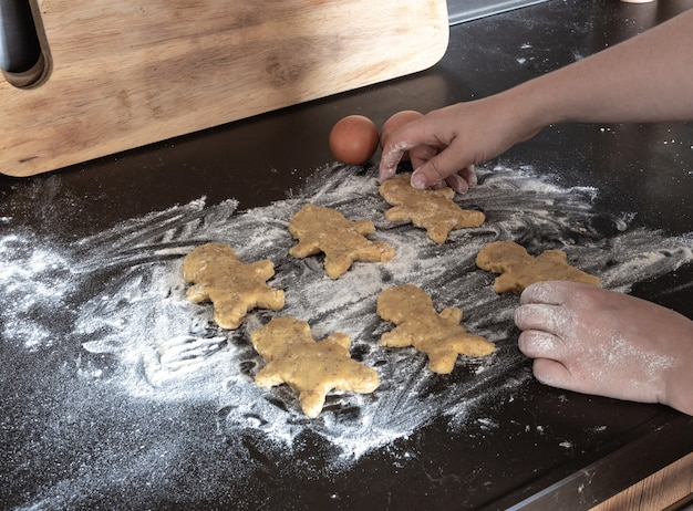Persona hornear galletas de hombre de pan de jengibre, persona manos en masa con flor en acogedora cocina
