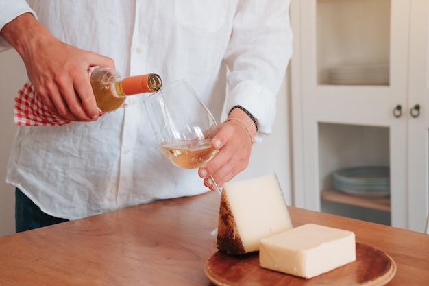Persona irreconocible agarrando una copa de vino blanco mientras tiene queso al lado para comer