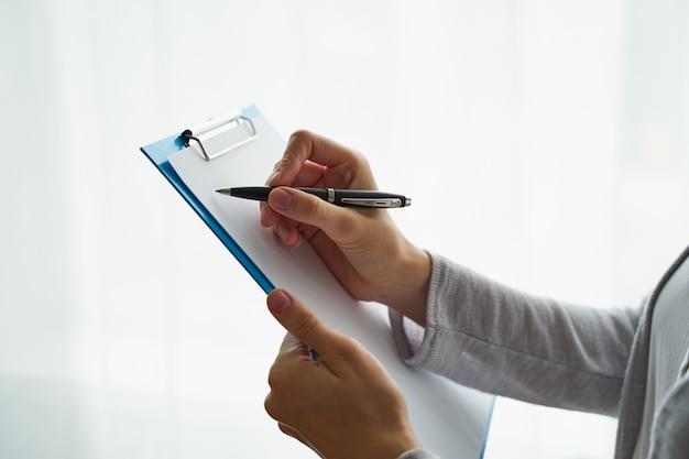 Persona irreconocible escribiendo en el portapapeles
