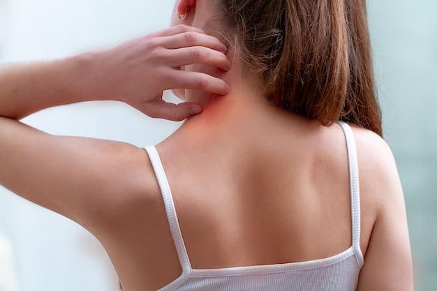 Persona joven que sufre de picazón en la piel y rascarse un lugar con picazón.