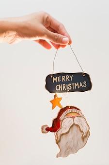 Persona con juguete con inscripción de feliz navidad