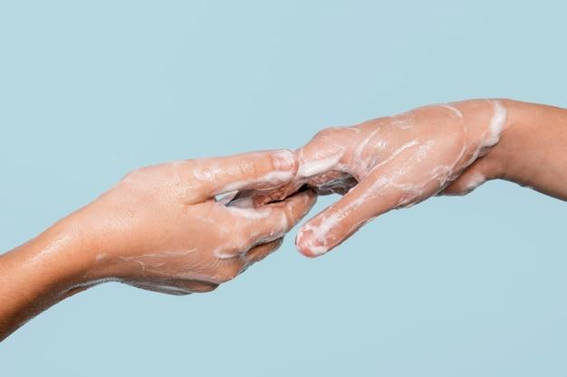 Persona de lado lavándose las manos aislado en azul