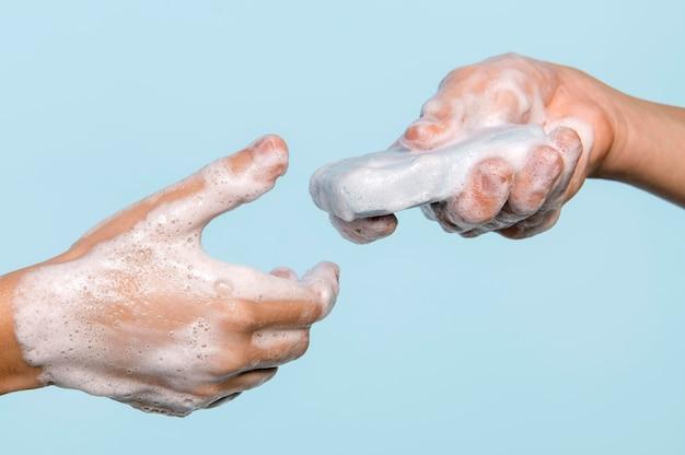 Persona de lado lavándose las manos con jabón