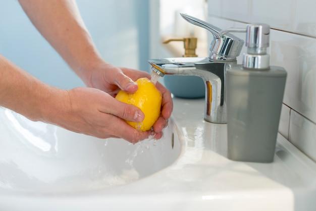 Persona lavando una manzana amarilla en el fregadero