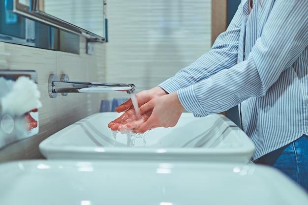 Persona lavándose las manos con agua corriente en el baño.