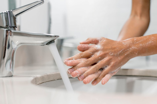 Persona lavándose las manos con jabón