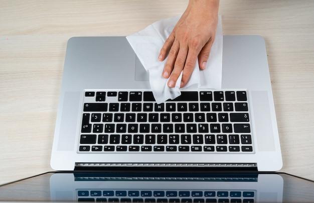 Persona limpiando laptop con toallitas con alcohol debido a coronavirus covid-19