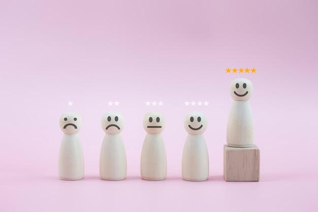 Persona de madera feliz modelo un smiley de 5 estrellas entre personas sobre fondo rosa pastel