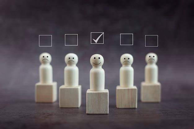 Persona de madera feliz modelo un smiley entre personas sobre fondo negro mejor excelente servicio empresarial