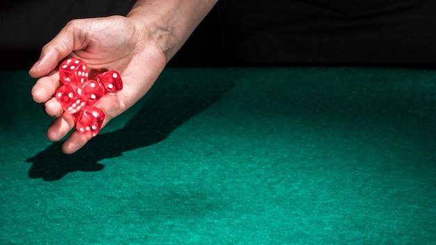Una persona mano rodando dados de casino rojo sobre la mesa verde