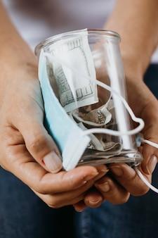 Persona con máscara médica y tarro transparente con dinero