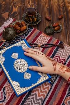 Persona con mehndi sosteniendo el corán cerca del té y dátiles frutales