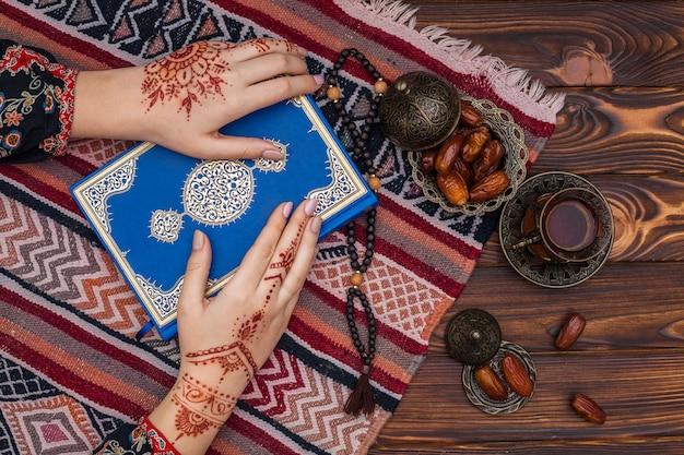 Persona con mehndi sosteniendo un libro de corán cerca de una taza de té