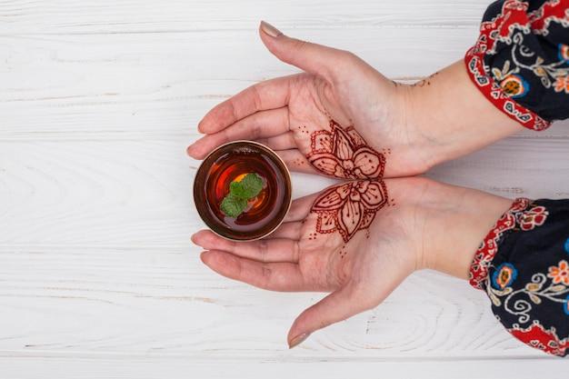 Persona con mehndi sosteniendo una taza pequeña de té