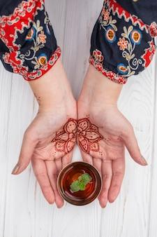 Persona con mehndi sosteniendo una taza de té
